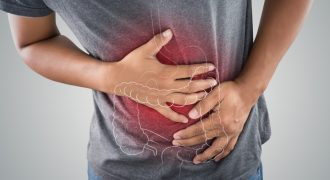 The photo of large intestine is on the man's body against gray background, People With Stomach ache problem concept, Male anatomy (The photo of large intestine is on the man's body against gray background, People With Stomach ache problem concept, Mal